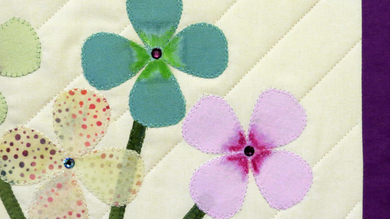 Flower detail on the wall hanging shows crayon and swarovski crystal embellishments.